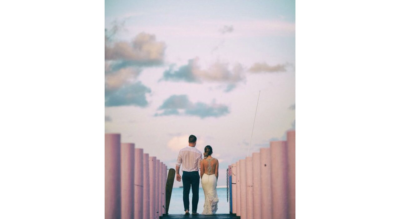 Newly wed couple walking down pier